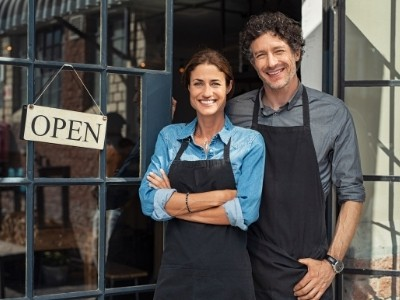 Small Business owners standing in front of open sign